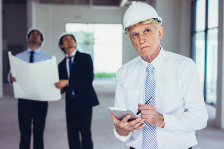 Pensive contractor analyzing building structure and making notes. Concentrated senior foreman in work helmet inspecting building inside while his colleagues looking around. Architecture concept