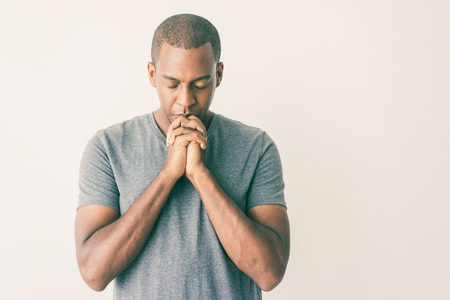 Photo for Calm spiritual handsome African guy praying with closed eyes. Serious peaceful young man with joining hands meditating. Belief concept - Royalty Free Image