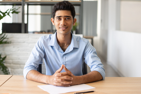 Foto de Portrait of happy Indian manager witting at table with paper. Young candidate sitting at job interview in office. Employment concept - Imagen libre de derechos