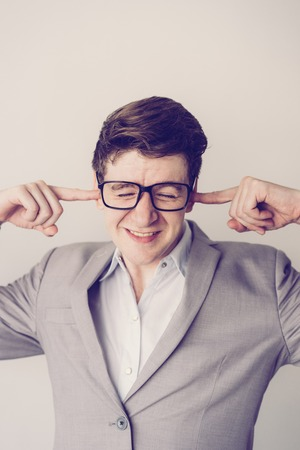 Photo pour Unhappy frustrated young businessman plugging ears by fingers because of noise. Stressed employee in eyeglasses annoyed with sounds. Negative emotion concept - image libre de droit