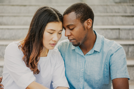 Foto de Portrait of sad multiethnic couple sitting together on stairs. Asian woman and African American man are tired or having problems. Reconciliation concept - Imagen libre de derechos