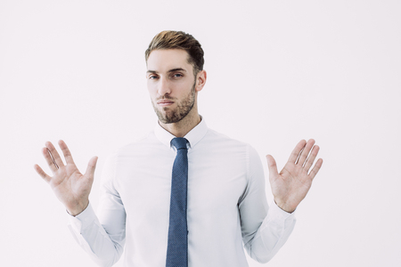 Business man raising hands and denying something. Attractive guy. Distrust concept. Isolated front view on white background.