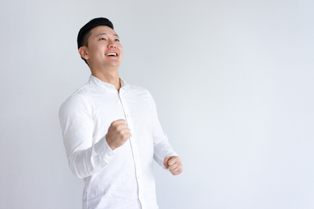 Foto de Cheerful Asian man pumping fists and looking away. Guy celebrating achievement. Success concept. Isolated front view on white background. - Imagen libre de derechos