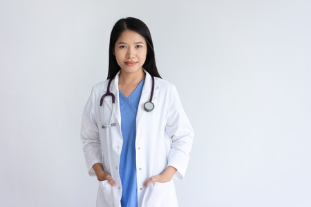 Photo pour Content young female doctor posing at camera. Pretty woman wearing white coat and standing. Medicine and healthcare concept. Isolated front view on white background. - image libre de droit