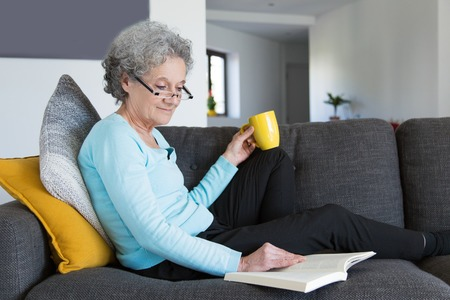 Photo pour Smiling positive retired lady excited with interesting novel. Grey haired senior woman in casual and eyeglasses resting on couch and reading book over cup of tea. Reading books concept - image libre de droit