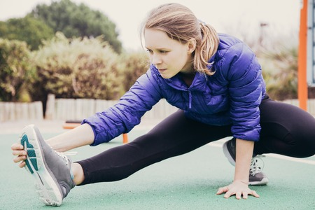 Foto de Focused athlete girl warming up outside. Young woman in sports winter jacket stretching leg on playground. Autumn or winter training concept - Imagen libre de derechos