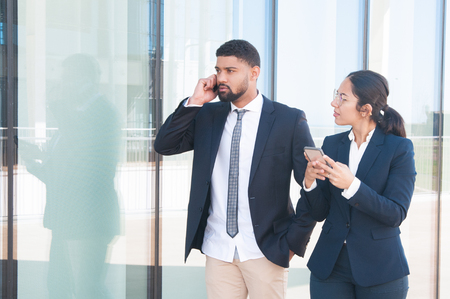 Photo pour Young successful business people using smartphones outdoors. Young woman in formal suit holding her gadget and looking at coworker, who speaking on cell. Phone users concept - image libre de droit