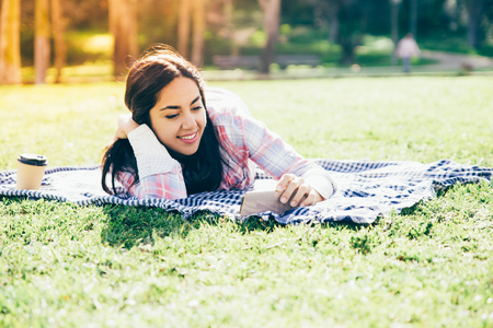 Peaceful delighted girl relaxing in park and watching movie on phone. Young woman in casual resting on grass, using smartphone and drinking takeaway coffee. Recreation concept