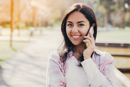 Cheerful student girl speaking on cell in city park. Beautiful young woman in casual checked shirt enjoying nice phone talk outdoors. Communication or positive emotions concept