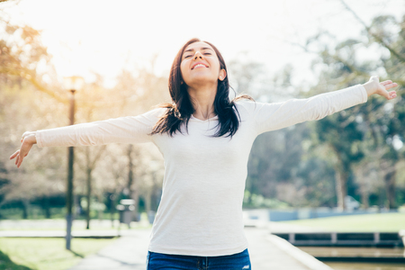 Carefree happy hipster girl enjoying nature in city park. Beautiful young woman in casual standing on footpath, spreading hands and turning face up. Enjoying nature concept