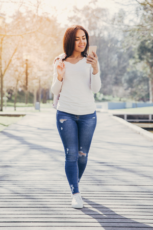 Photo for Focused positive girl chatting on phone. Beautiful young woman in casual smiling at smartphone screen while walking along footpath in park. Communication concept - Royalty Free Image