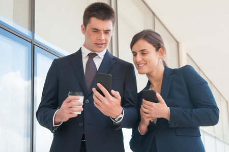 Photo for Puzzled manager with takeaway cup showing smartphone screen to female coworker. Two colleagues with phones sharing news during coffee break. Sharing news concept - Royalty Free Image