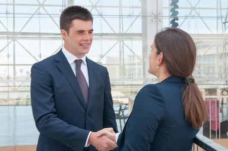 Photo for Two colleagues saying hello to each other on office terrace. Young man and woman in formal suits handshaking. Business communication concept - Royalty Free Image