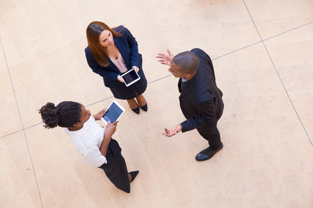 Photo pour Three coworkers discussing project in office lobby. Top view of mix raced team of people in formal clothes standing on concrete floor, holding tablets, talking and gesturing. Business talk concept - image libre de droit