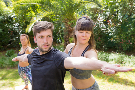 Photo for Focused yoga instructor helping newby to cope with warrior pose. Man doing yoga outdoors, woman adjusting his hands. Training yoga concept - Royalty Free Image