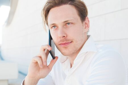 Photo for Focused business man calling on smartphone outdoors. Guy using mobile phone with building wall in background. Communication in business concept. Front view. - Royalty Free Image