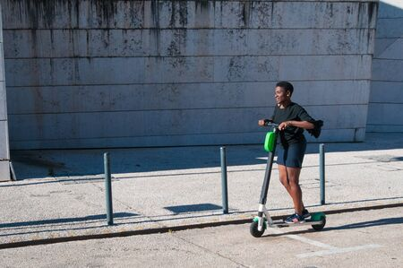 Photo pour Smiling black woman enjoying riding electric scooter outdoors. Young woman wearing casual blouse and skirt with building in background. Modern transportation concept. Side view. - image libre de droit