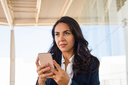 Photo pour Young woman using mobile phone. Beautiful brunette woman using smartphone and looking away. Technology concept - image libre de droit