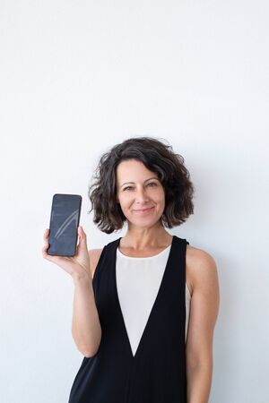 Photo pour Happy confident woman advertising online mobile app. Joyful middle aged curly haired woman in casual showing blank phone screen at camera. Mobile app concept - image libre de droit