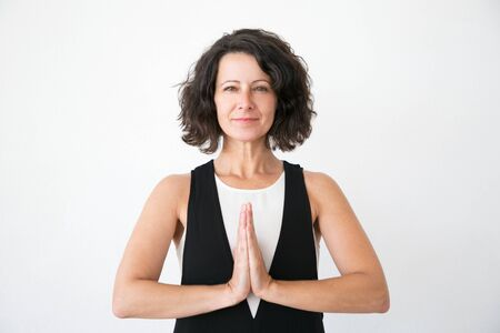 Foto de Smiling peaceful woman in casual practicing yoga and meditation. Calm middle aged woman making Namaste gesture and looking at camera. Yoga concept - Imagen libre de derechos