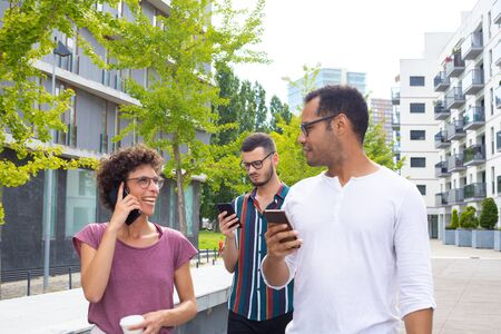 Photo pour Joyful couple with cellphones talking to each other. Two men holding smartphone, woman with coffee talking on mobile phone and laughing. Mobile technology concept - image libre de droit