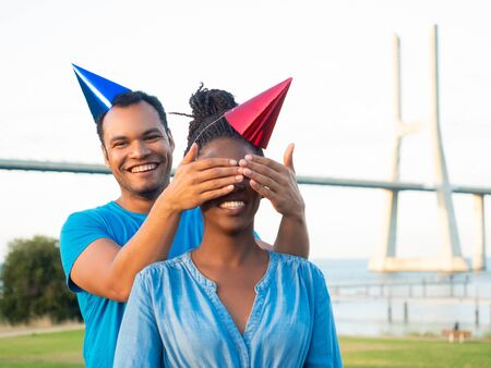 Smiling young man making surprise for his friend. Handsome man covering eyes of beautiful African American woman. Concept of birthday surprise