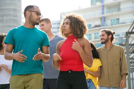 Photo pour Interracial team of friends walking outside. Young men and women in casual enjoying walk, talking, discussing news. Communication and lifestyle concept - image libre de droit