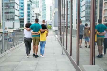Photo for Team of male and female friends enjoying outdoor walk. Back view of mix raced people walking down city street, hugging each other and talking. Polygamy concept - Royalty Free Image