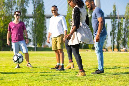 Foto de Group of four happy friends kicking ball in park. Smiling young people having fun together. Leisure concept - Imagen libre de derechos