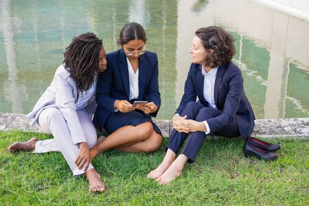 Photo for Barefoot businesswomen with smartphone outdoor. High angle view of multiethnic female colleagues sitting on green lawn and using mobile phone. Technology concept - Royalty Free Image