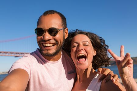 Photo pour Happy excited couple enjoying vacation and taking selfie on city promenade. Man and woman standing outside, posing and showing peace sign at phone camera. Vacation concept - image libre de droit