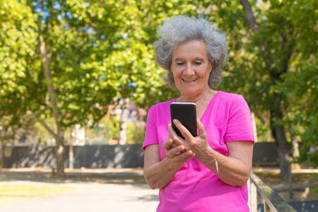 Joyful happy old lady using cellphone for video call in park. Senior grey haired woman in casual standing on walkway, using mobile phone and smiling. Communication concept