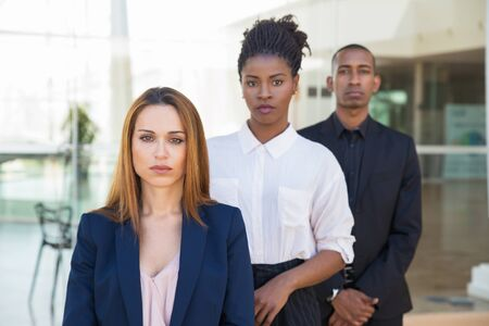 Diverse business colleagues posing in office. Line of serious multiethnic business man and women looking at camera. Confident team concept