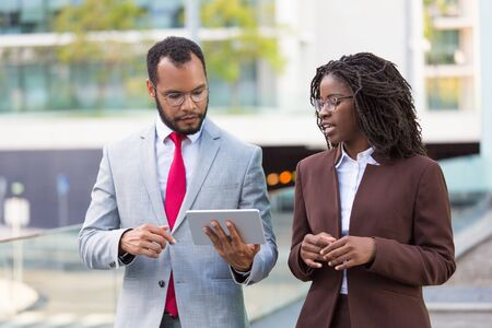 Foto de Multiethnic business team watching presentation on tablet on their way to office. Business man showing tablet screen to black female colleague while walking outdoors. Wi-Fi connection concept - Imagen libre de derechos