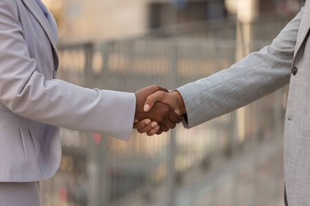 Foto de Closeup of handshake. Business man and woman in office suits shaking hands. Dealing concept - Imagen libre de derechos