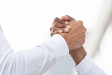 Photo pour Closeup of arm wrestling or friendly handshake gesture. Diverse business people shaking hands. Business communication concept - image libre de droit