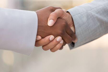Photo pour Closeup of multiethnic business colleagues handshake. Diverse business man and woman shaking hands. Collaboration concept - image libre de droit