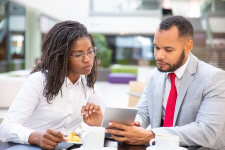 Foto de Serious business colleagues watching content on tablet together. Diverse business man and woman sitting in cafe, holding tablet and looking at screen. Media content concept - Imagen libre de derechos