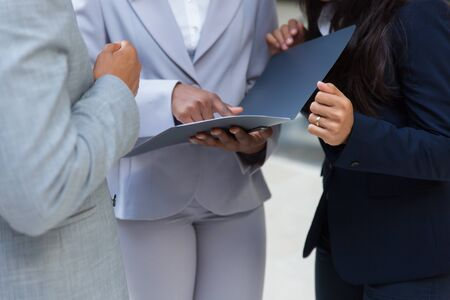 Photo pour Cropped shot of business people with folder. Mid section of business colleagues standing together and looking at papers in folder. Teamwork concept - image libre de droit