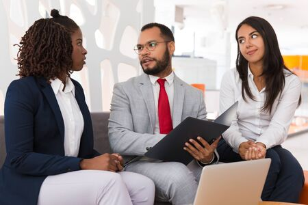 Foto de Diverse business colleagues discussing project report. Business man and woman sitting on office couch with open folder and talking. Paperwork concept - Imagen libre de derechos