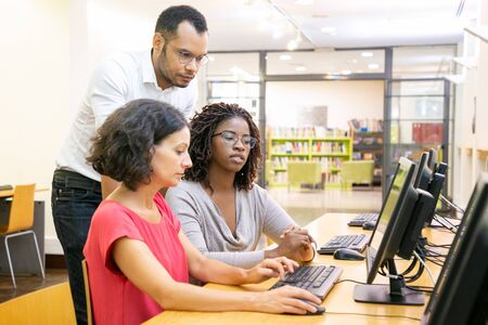 Foto de Teacher helping trainees in computer class. Man and women sitting and standing at desk, using desktop, looking at monitor and talking. Training concept - Imagen libre de derechos