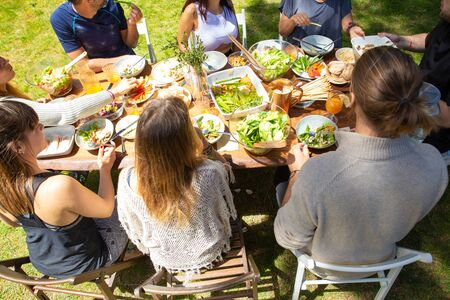 Young friends at table outdoor. High angle view of male and female friends gathering around table with healthy dishes in backyard. Healthy eating and friendship concept