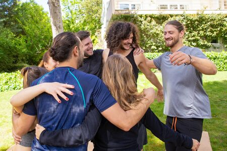 Foto per Cheerful young people hugging outdoor. Smiling young men and women in sportswear gathering together in park for yoga practice. Yoga concept - Immagine Royalty Free