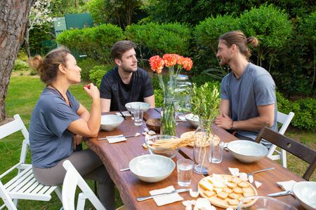 Photo pour Smiling people talking in backyard. Cheerful young male and female friends sitting at table with organic meal and talking outdoor. Gathering together concept - image libre de droit