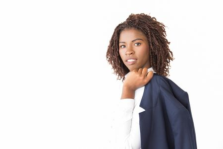 Photo pour Confident female business leader holding jacket over shoulder. Young African American business woman posing isolated over white background, looking at camera. Confident businesswoman concept - image libre de droit