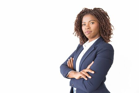 Foto de Serious successful professional posing in studio. Young African American business woman with arms crossed standing isolated over white background, looking at camera. Confident businesswoman concept - Imagen libre de derechos