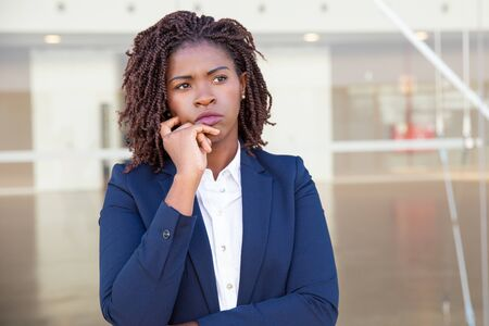 Photo pour Focused pensive leader thinking outside. Serious young black business woman standing at outdoor glass wall, touching chin and looking away into distance. Thinking concept - image libre de droit