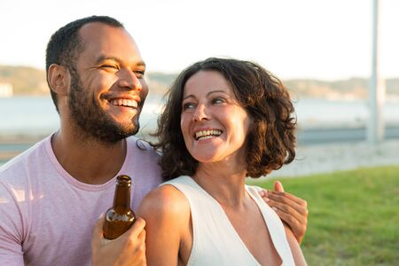 Photo pour Happy relaxed couple drinking beer, and chatting outdoors. Man and woman sitting on grass, hugging, holding beer bottle and laughing. Dating outdoors concept - image libre de droit