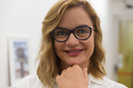 Photo pour Confident businesswoman smiling at camera. Close-up portrait of beautiful middle aged businesswoman in eyeglasses standing with hand on chin and smiling at camera. Business concept - image libre de droit