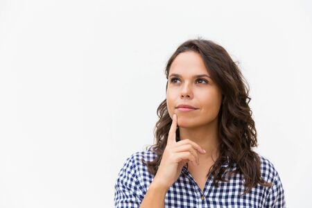 Photo pour Dreamy pensive female customer touching chin with finger and looking away at copy space. Young woman in casual checked shirt standing isolated over white background. Advertising concept - image libre de droit